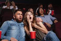 Jeunes couples choqués observant un film d'horreur Photos stock