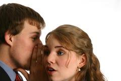 Jeunes couples chuchotant au travail Image libre de droits