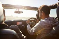 Jeunes couples conduisant avec le toit ouvrant ouvert, passager arrière POV image libre de droits