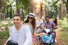 Jeunes couples conduisant la liberté de scooter et le voyage des jeunes de concept d'aventure par Forest Cheerful Friends tropica Images stock