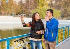 Jeunes couples confus au sujet des directions en parc Image stock