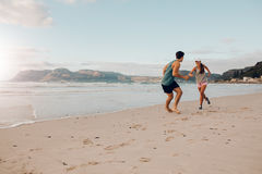 Jeunes couples convenables jouant sur la plage Photo libre de droits