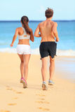 Jeunes couples courants pulsants de forme physique sur le sable de plage Photo stock