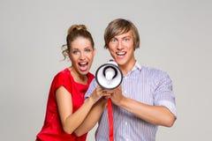 Jeunes couples criant dans le corne de brume Photographie stock