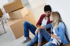 Jeunes couples déballant des boîtes en carton à la nouvelle maison se déplaçant le concept Image libre de droits