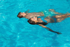 Jeunes couples décontractés dans la piscine Photographie stock libre de droits