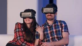 Jeunes couples décontractés dans le film de observation de casque de vr se reposant sur un sofa Image libre de droits