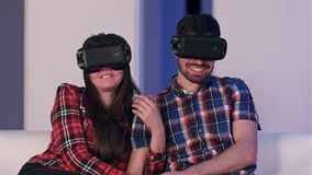 Jeunes couples décontractés dans le film de observation de casque de vr se reposant sur un sofa