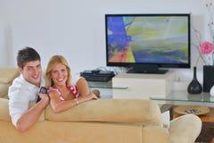 Jeunes couples décontractés regardant la TV à la maison Photographie stock