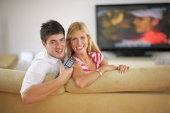 Jeunes couples décontractés regardant la TV à la maison Images stock