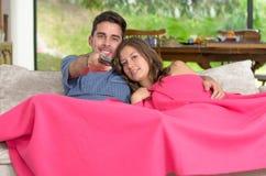 Jeunes couples décontractés regardant la TV à la maison dans lumineux Photos stock