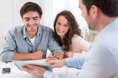 Jeunes couples décontractés rencontrant un vrai agent immobilier Image stock
