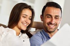Jeunes couples décontractés travaillant sur l'ordinateur portable à la maison Photo libre de droits