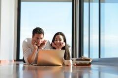 Jeunes couples décontractés travaillant sur l'ordinateur portable à la maison Photographie stock libre de droits