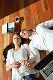 Jeunes couples décontractés travaillant sur l'ordinateur portable à la maison Image stock