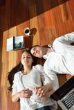 Jeunes couples décontractés travaillant sur l'ordinateur portable à la maison Photographie stock
