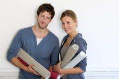 Jeunes couples décorant la maison avec des papiers peints Photo stock