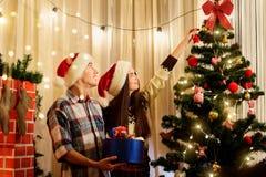 Jeunes couples décorant un arbre de Noël avec des jouets à Noël Images libres de droits