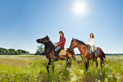 Jeunes couples dépensant des chevaux d'équitation de temps ensemble Photographie stock libre de droits