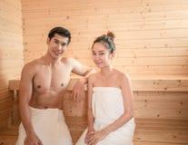 Jeunes couples détendant à l'intérieur d'un sauna Photos libres de droits