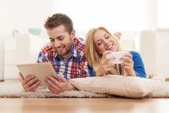 Jeunes couples détendant à la maison Images stock