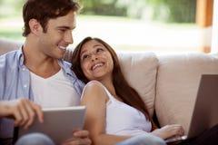 Jeunes couples détendant avec l'ordinateur portable et le comprimé à la maison Photos stock
