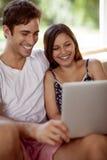 Jeunes couples détendant avec un ordinateur portable Image stock