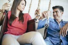 Jeunes couples détendant dans l'oscillation image stock