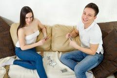 Jeunes couples détendant et jouant des cartes sur la couverture et les oreillers Photographie stock