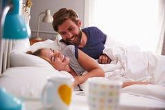 Jeunes couples détendant et riant dans le lit ensemble images stock