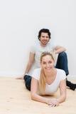Jeunes couples détendant sur le plancher d'une nouvelle maison Photographie stock