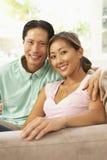 Jeunes couples détendant sur le sofa à la maison Photographie stock libre de droits
