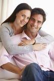 Jeunes couples détendant sur Sofa Together At Home Image stock