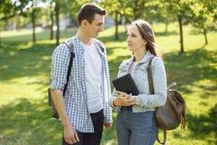 Jeunes couples d'étudiant marchant en parc et parler Photo stock