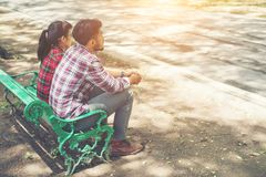 Jeunes couples d'adolescents dans l'amour se reposant ensemble sur le banc dedans Image stock