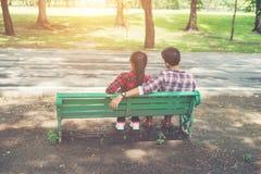 Jeunes couples d'adolescents dans l'amour se reposant ensemble sur le banc dedans Photos stock