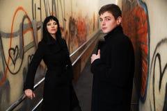 Jeunes couples d'affaires au mur grunge de graffiti Photographie stock