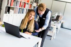 Jeunes couples d'affaires utilisant l'ordinateur portable dans le bureau Image stock