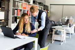 Jeunes couples d'affaires utilisant l'ordinateur portable dans le bureau Photos libres de droits