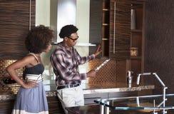Jeunes couples d'Afro-américain dans la nouvelle cuisine meublée choisissant des matériaux Photos stock