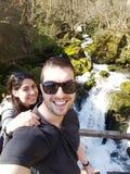 Jeunes couples d'amour dans la montagne sur un fond de cascade Images stock
