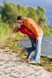Jeunes couples d'amour embrassés sur la côte du fleuve Photos libres de droits