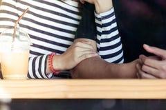 Jeunes couples d'amour tenant des mains ensemble dans le café Images stock