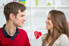 Jeunes couples d'amour tenant le coeur de la valentine rouge ensemble Images libres de droits