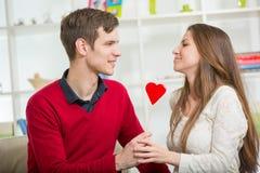 Jeunes couples d'amour tenant le coeur rouge de valentines ensemble Photographie stock