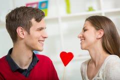 Jeunes couples d'amour tenant le coeur rouge de valentines ensemble Images libres de droits