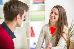 Jeunes couples d'amour tenant le coeur rouge de valentines ensemble Photos stock