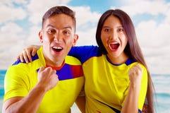 Jeunes couples d'ecuadorian portant l'appareil-photo debout de revêtement de marathon de chemise officielle du football, langage  Photo stock