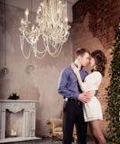 Jeunes couples d'histoire d'amour dans l'intérieur avec chadelier et la cheminée Photos libres de droits