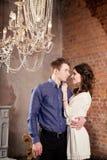 Jeunes couples d'histoire d'amour dans l'intérieur avec le lustre et la cheminée Photographie stock libre de droits